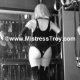 Dominatrix Mistress Troy wearing black patent-leather thigh-high stiletto-heeled boots with black latex leotard and opera length gloves