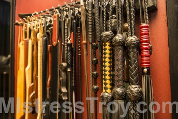 MISTRESS TROY Pro-Domme Manhattan NYC New York uses implements for spanking and corporal punishment on male slaves,             submissives, masochists and fetishists in Her dungeon