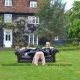 The Baroness Essex and Mistress Troy relax on a serene lawn in England
