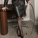 Fem-Domme Mistress Troy in Her leather business suit with Her black leather signal whip